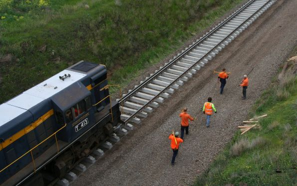 Workers go to check up on the unballasted track after T413 passes
