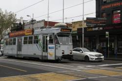 Wanker in a Mercedes Benz speeds past tram Z3.159 stopped at a tram stop on Racecourse Road, Flemington