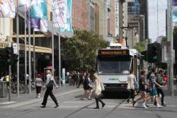 Clueless pedestrians ignore moving trams at the corner of Bourke and Swanston Street