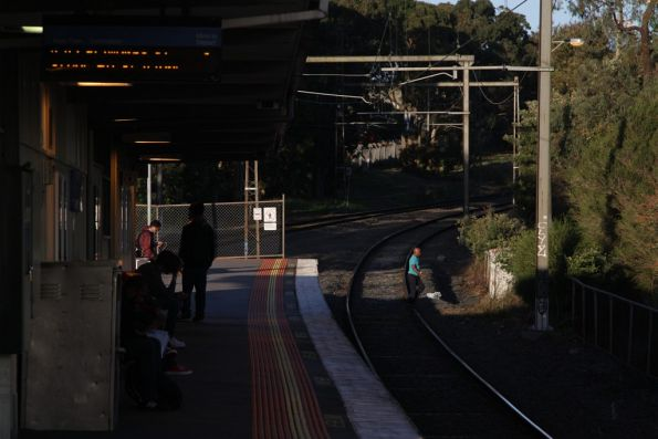 Pedestrian walks across the tracks at the down end of Syndal station