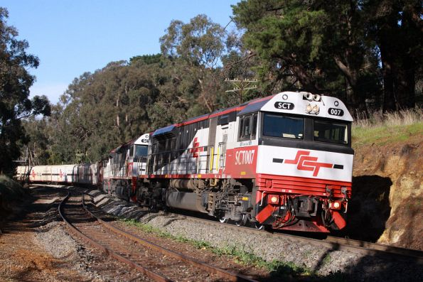 Through a gap in the shadows, SCT007 leads SCT014 and SCT008 on the westbound train at Mt Lofty