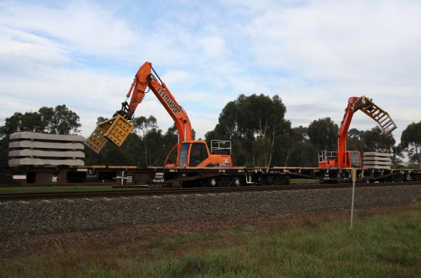 Ballet of excavators moving sleepers onto the train at Inverleigh