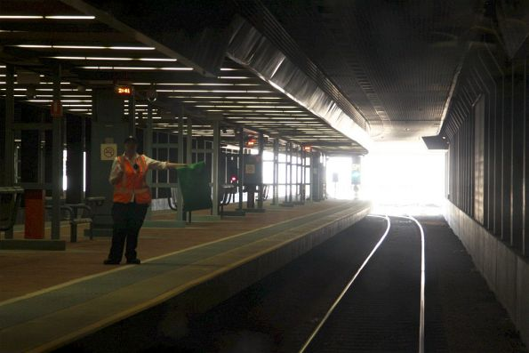 Passenger service assistant giving the driver a green flag on departure from Adelaide station