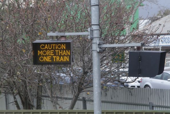 'Caution more than one train' sign illuminated at a level crossing outside Emerson station