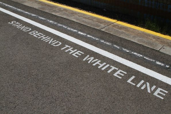 'Stand behind the white line' signage at Glanville station