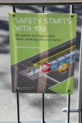 'Safety starts with you - take care walking around trams' poster at a tram stop