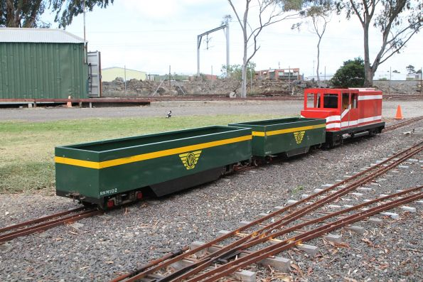 Fictional locomotive and two riding cars parked between runs