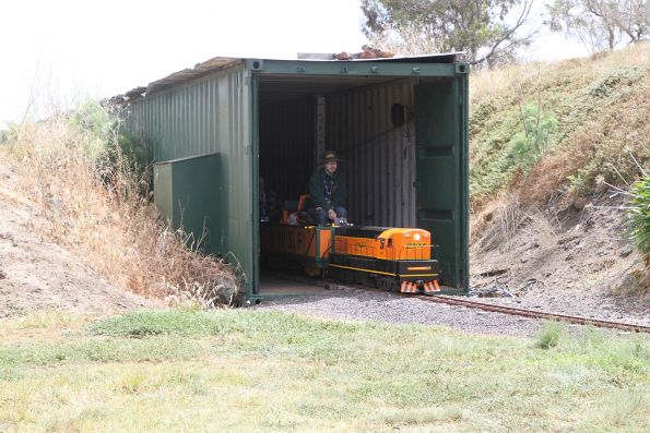 BNSF locomotive leads a train out of a tunnel made from shipping containers