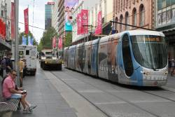 Tram C2.5111 advertising 'Target' passes the tilt tray truck