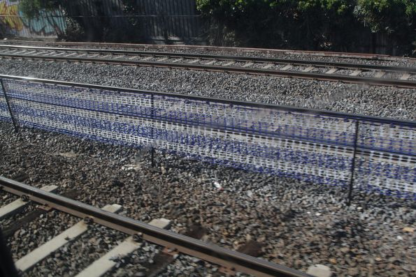 Blue and white coloured safety barrier mesh separates the suburban and ARTC tracks at Middle Footscray