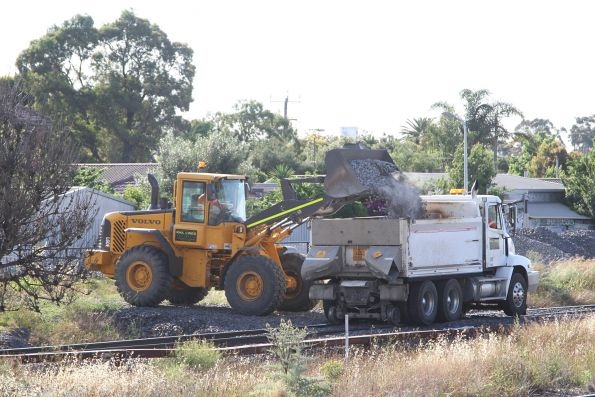 Front end loader places ballast into a hi rail tip truck on the standard gauge line at Sunshine