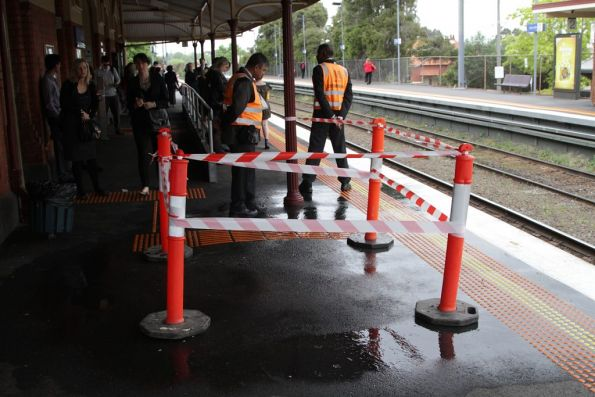 Authorised officers guard a water leak in the platform at Ascot Vale