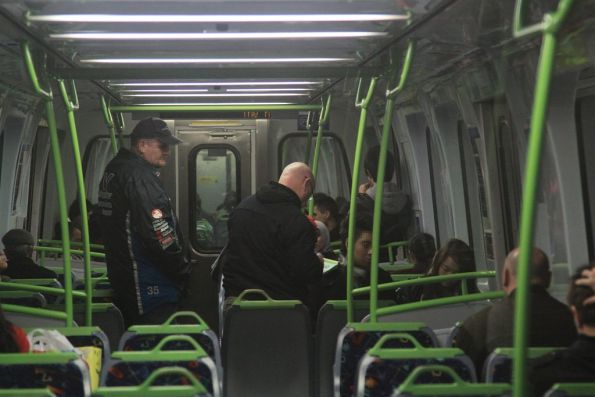 Undercover ticket inspectors write up a passenger onboard a Metro train