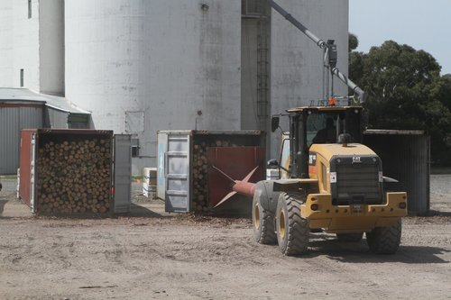 Specially fitted loader pushes the logs into a 40 footer container