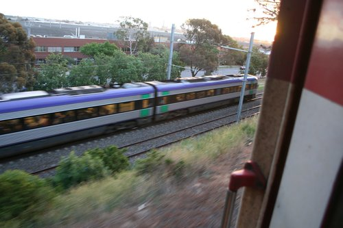 VLocity speeds past on the passenger lines down below