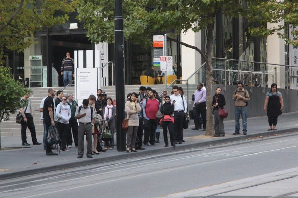 Crowds of passengers wait outside Southern Cross Station for the next bus to Port Melbourne