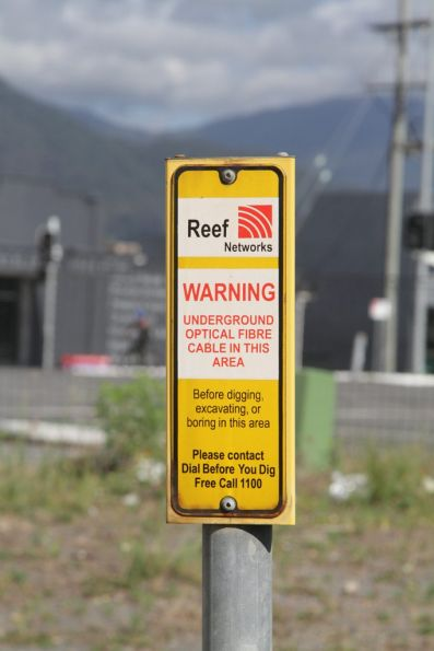 Reef Networks optical fibre cable warning sign beside a railway line