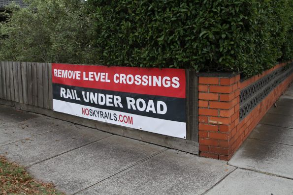 'Remove Level Crossings / Rail Under Road / NoSkyrails.com' poster on a house backing onto the railway at Carnegie