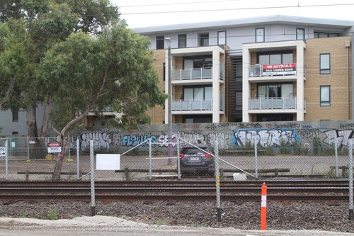 'No Skyrails - Rail Under Road' banner tied to the balcony of a third story apartment at Hughesdale