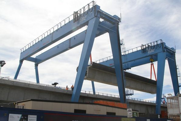 Pair of portal cranes at work moving a completed bridge span at Murrumbeena station