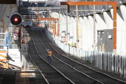 Worker crosses the tracks between Murrumbeena and Hughesdale