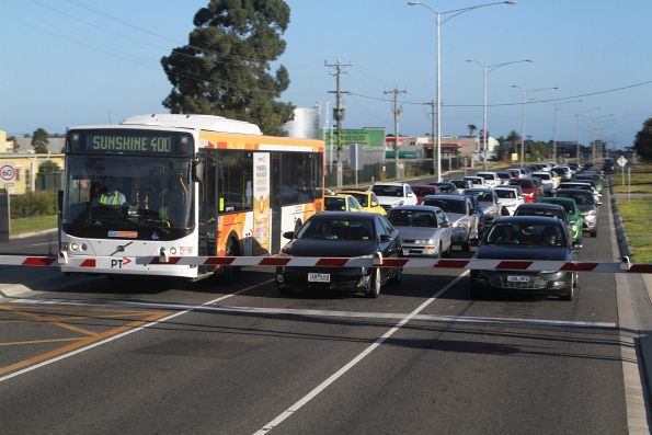 CDC Melbourne bus on route 400 stuck at the level crossing in Deer Park