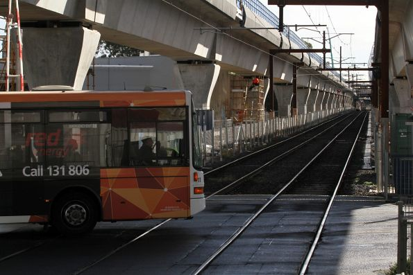 CDC Melbourne bus #11 from Oakleigh depot crosses the Murrumbeena Road level crossing at Murrumbeena