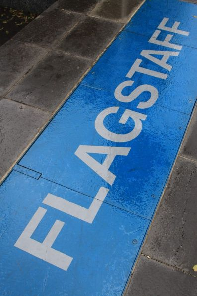 Flagstaff nameboard facing the sky outside the station entrance