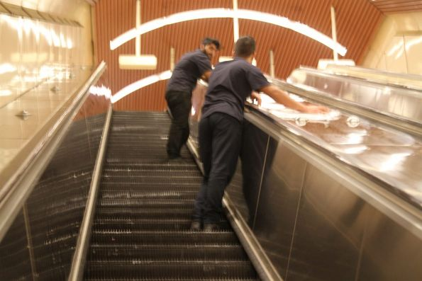 Cleaners at work wiping down the escalators at Flagstaff station