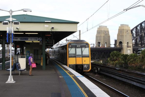 Tangara T94 arrives into Milsons Point, with the Sydney Harbour Bridge behind