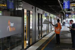 Platform staff waves the 'all clear' flag to an empty platform at Circular Quay
