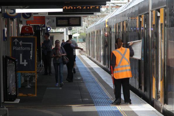 Sydney Trains station staff waves the white departure flag to the guard of a waiting train at Campbelltown