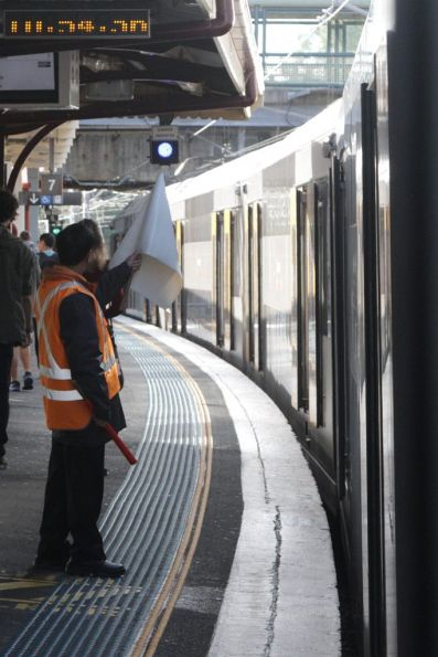 Station staff wave the white 'all clear' flag at Redfern station