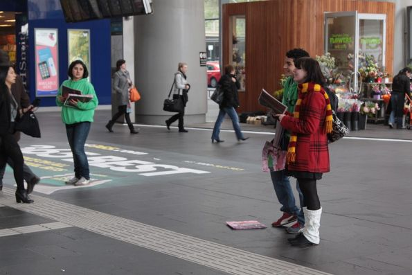 Handing out copies of free newspaper 'Melbourne Weekly' at the main entrance to Southern Cross Station