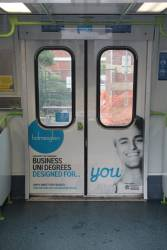 Holmesglen TAFE advertising on the doors of a Comeng train