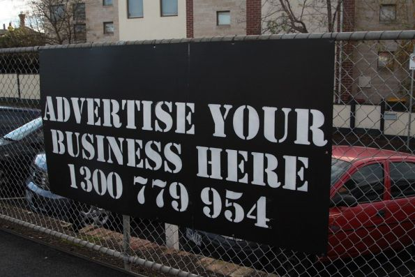 'Advertise your business here' sign at a suburban station, made of corrugated plastic