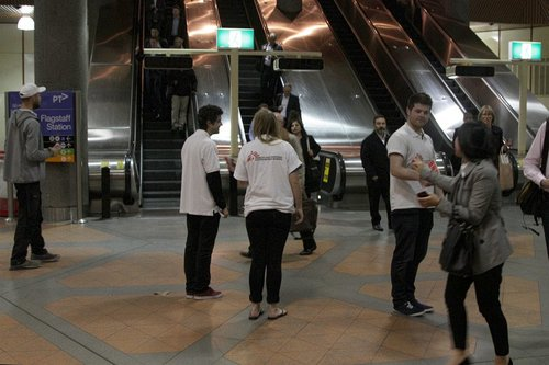 Street fundraisers at work in the unpaid area of Flagstaff station during evening peak