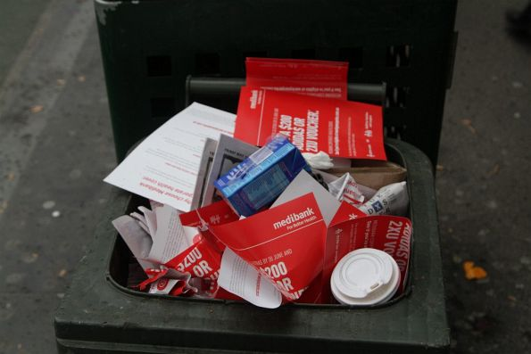 Rubbish bin outside Flagstaff station, full of unwanted Medibank Private flyers