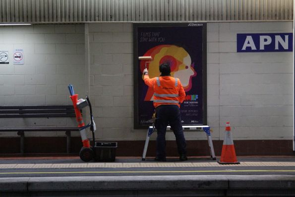 Changing over the advertising posters at Box Hill station