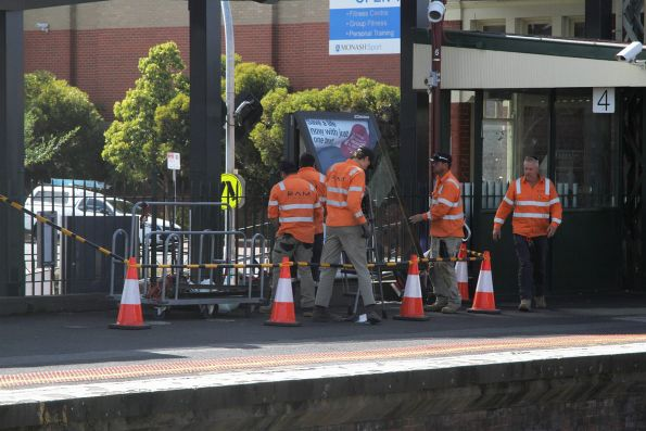 Contractors remove the JCDecaux advertising panels at Caulfield station