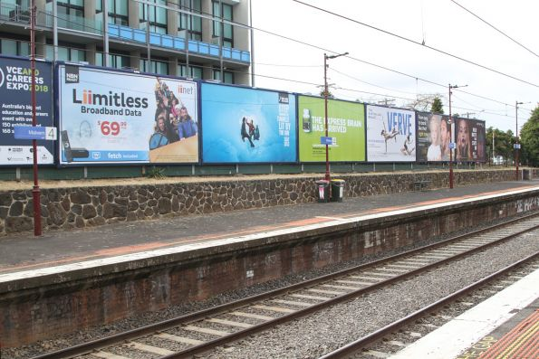 Malvern station platform 4 lined with advertising billboards