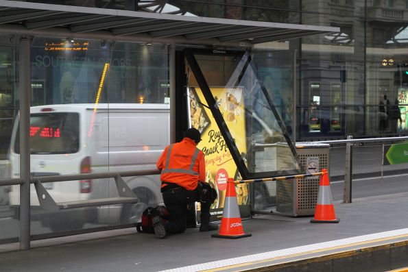 JCDecaux staff fixing a stalled advertising screen at a Spencer Street tram stop