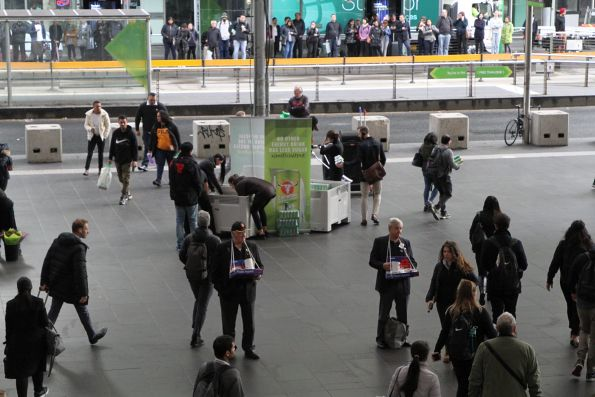 Volunteer Poppy Appeal collectors in front of an energy drink promotion at Southern Cross Station