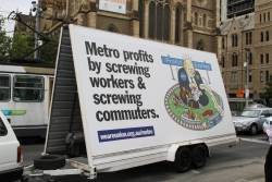 Rail, Tram and Bus Union 'Metro profits by screwing workers and commuters' billboard driving past Flinders Street Station
