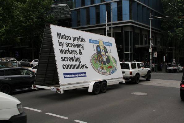 Rail, Tram and Bus Union 'Metro profits by screwing workers and commuters' billboard driving down King Street