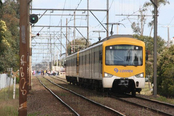Siemens train departs Clayton on the up, as passengers cross the reopened level crossing