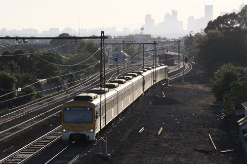 Siemens train departs Middle Footscray under a hazy sky
