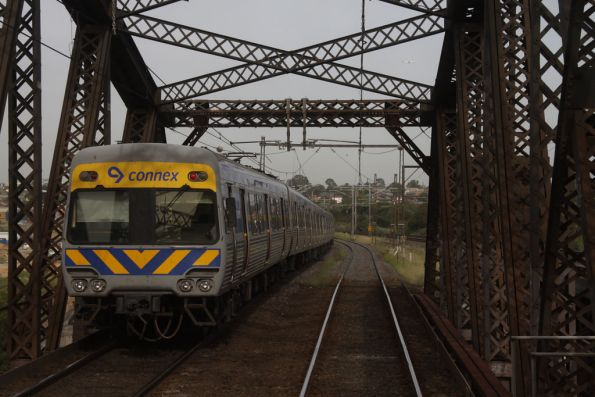 Alstom Comeng train passes under the Maribyrnong River bridge on a down Werribee service