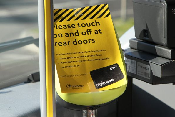 'Please touch on and off at the rear doors' sign on the myki reader onboard a Transdev bus