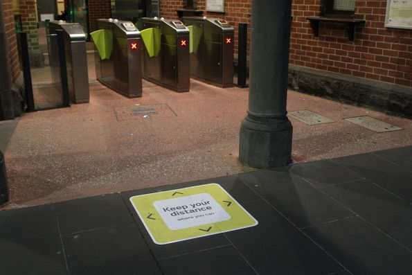 'Keep your distance where you can' signage at the Footscray station ticket gates